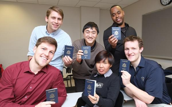 Six students pose with their passports.